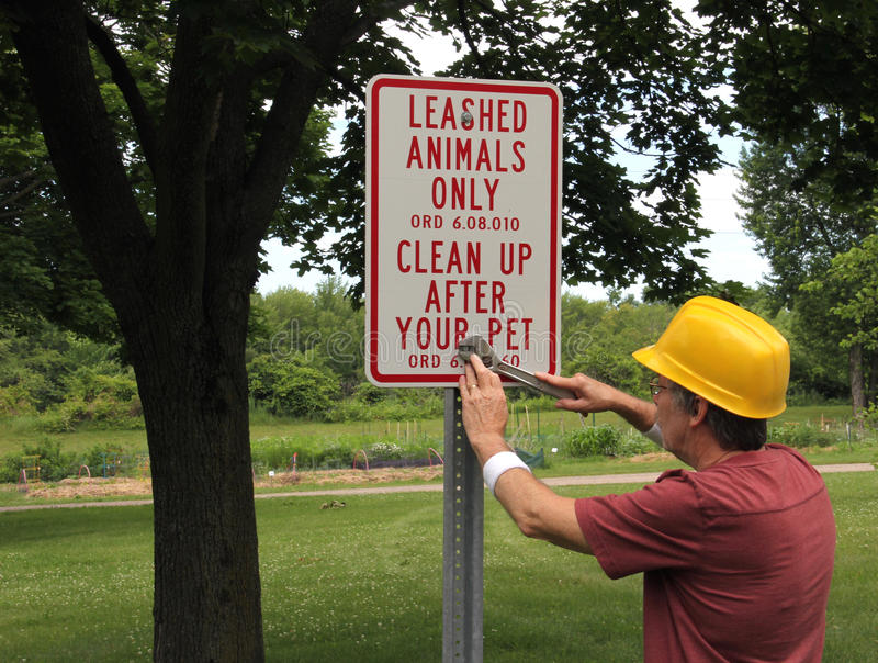Park worker installing animal sign. Park worker using a wrench to install an animal sign stock images