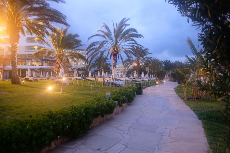Park zone in empty resort place in the seaside with hotel buildings and palm trees near walk path in low season with night lightin stock photography