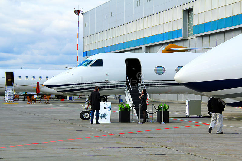 The parked aircraft. Parking aircraft near a large hangar stock photo