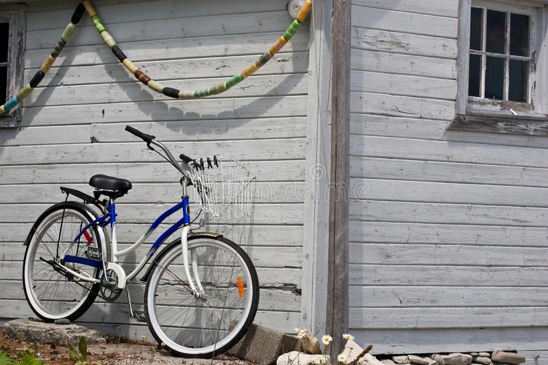 Parked bicycle beside boathouse. A new retro style bicycle parked up against an aging boathouse stock photography