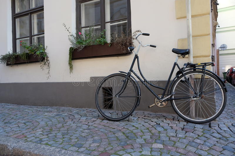 Parked bicycle in narrow street. Parked bicycle in narrow street in the old town of Riga, vintage style stock image