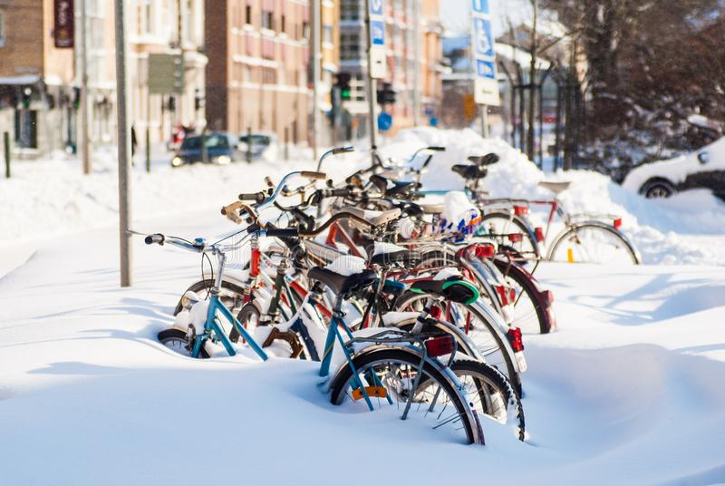 Parked bicycles covered in snow after heavy snowfall. royalty free stock images
