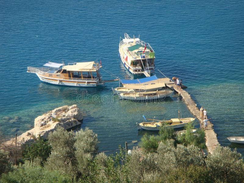 Parked boats on the sea in Turkey. Different kind of boats. Blue quiet sea. Seen by the tall one. Trees and plants in foreground. Rocks on the sea. Wood small stock photos
