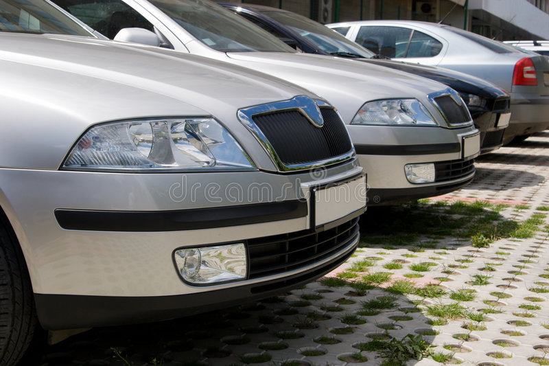 Parked cars, close-up. A row of similar cars parked in a parking lot, close-up royalty free stock photo