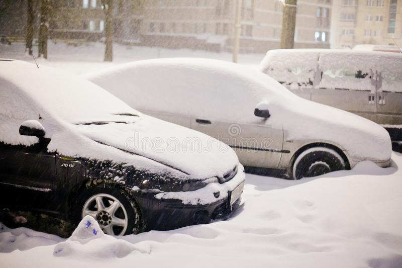 Parked cars covered with thick layer of heavy snow in December royalty free stock images