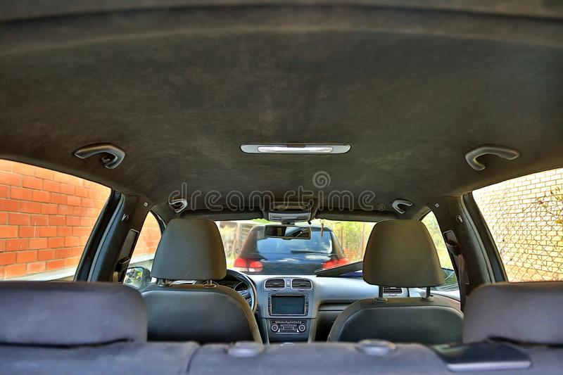 Parked cars at home. View from inside the car. Interior of a modern car with black alcantara ceiling stock photos