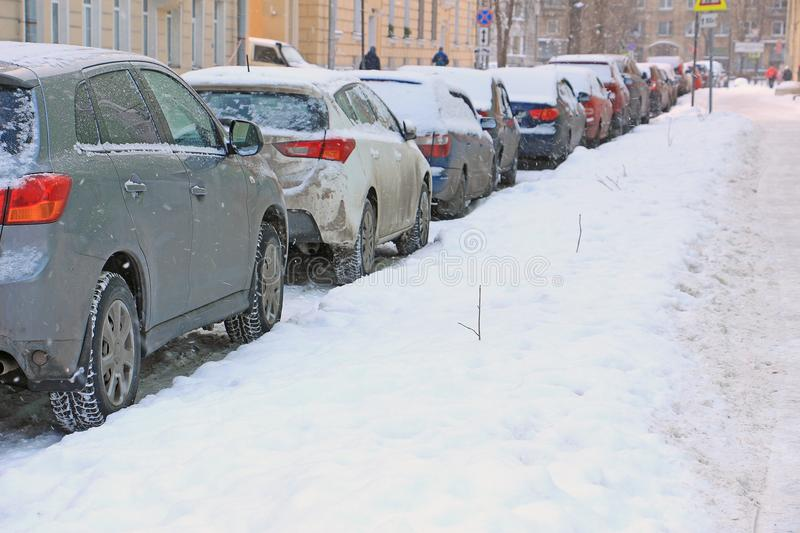 Parked cars on the roadside during a snowfall stock photo