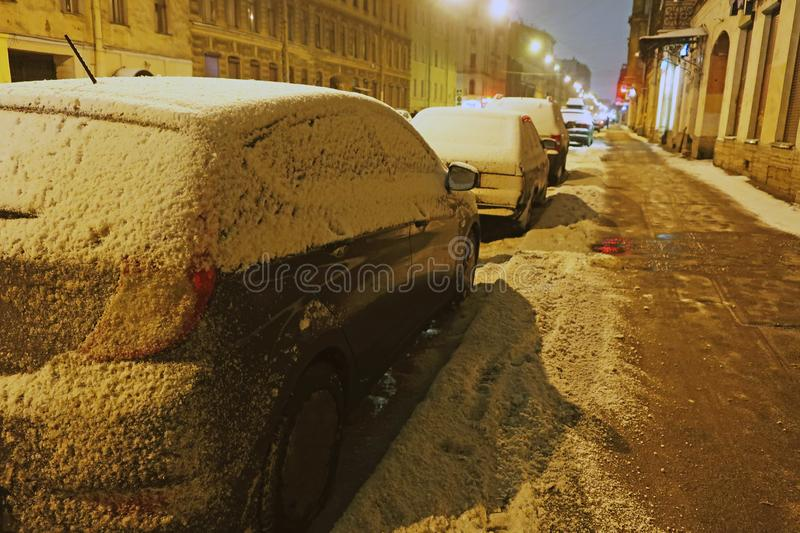 Parked cars swept by snow. Parked cars swept by the snow on the morning street of the city royalty free stock photos