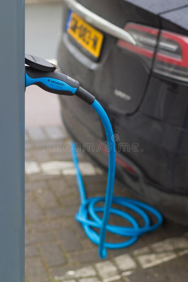 Parked hybrid electric car on busy city street charging with electric plug in power station. The Hague, the Netherlands - 26 January 2019: parked hybrid electric royalty free stock photo