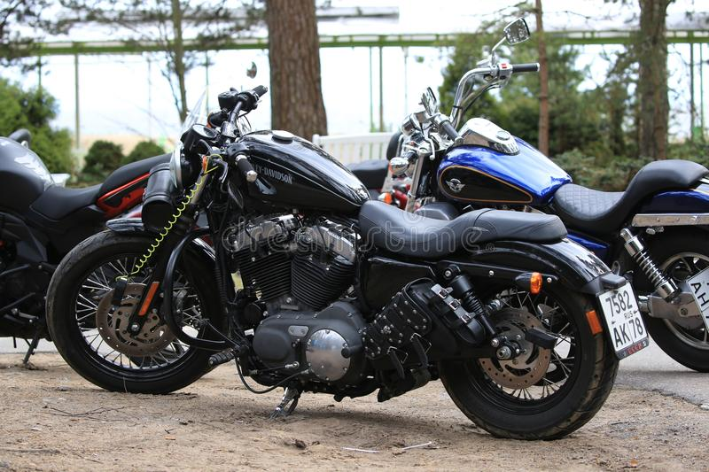 Parked motorcycle Harley Davidson Sportster 1200 black outdoors on a cloudy day. Look on the left side. Time of opening of motoseason 2018. Komarovo. Resort area royalty free stock photography