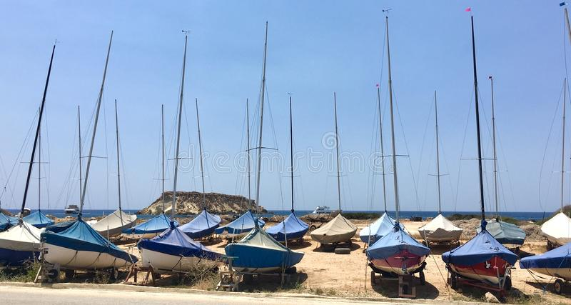 Parked sailboats. Group of small sailboats parked in a row on a dried soil stock image