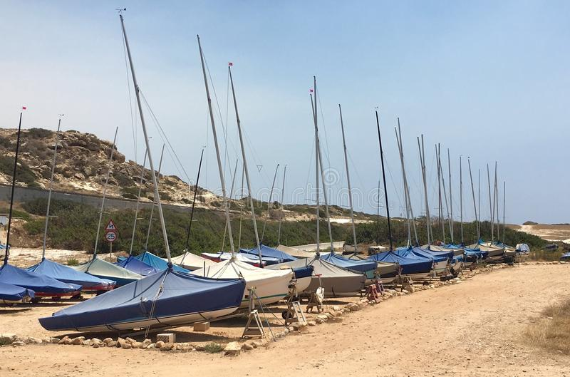 Parked sailboats. Group of small sailboats parked in a row on a dried soil royalty free stock photos
