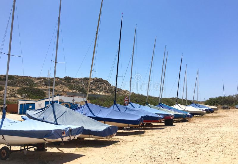 Parked Sailboats. Group of small sailboats parked in two rows on dried soil stock images