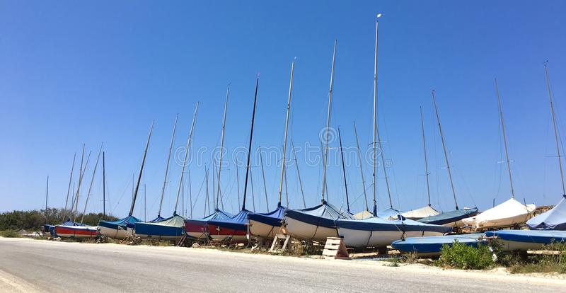 Parked Sailboats. Group of small sailboats parked in two rows on dried soil stock photo