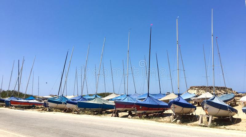 Parked Sailboats. Group of small sailboats parked in two rows on dried soil stock photography