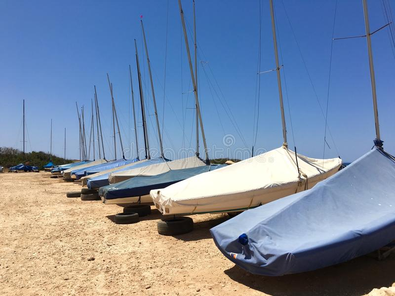 Parked Sailboats. Group of small sailboats parked in two rows on dried soil royalty free stock photo