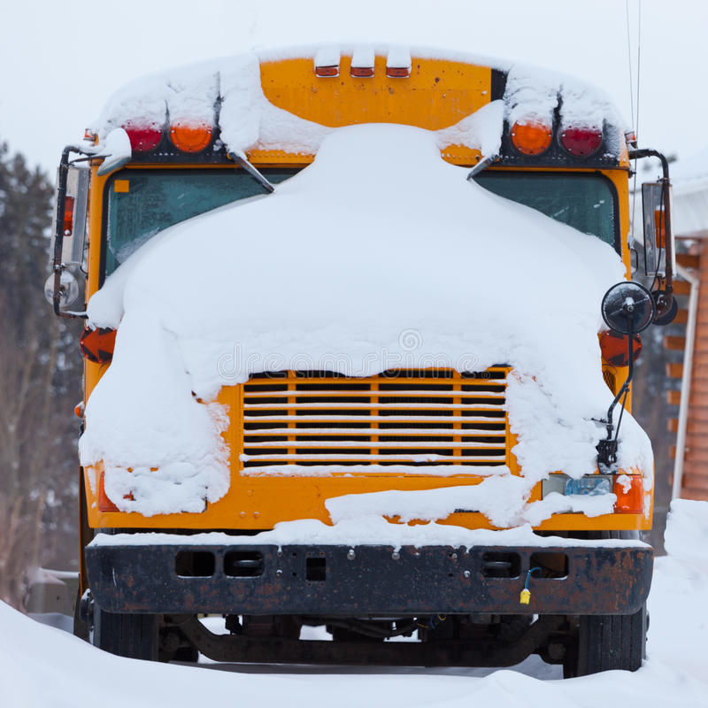 Parked school bus winter blizzard snow cover. Snow covered front of parked school bus after heavy winter blizzard snow fall stock image