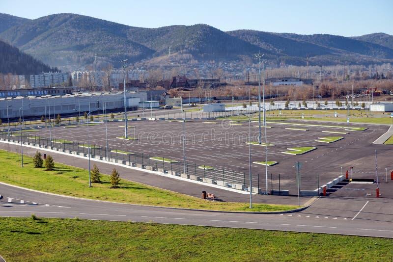 Parken für Fahrzeuge nahe dem Sportzentrum der Platin-Eis-Arena in den Nachbarschaft ruhigen Dämmerung, errichtet für den Winter lizenzfreies stockfoto