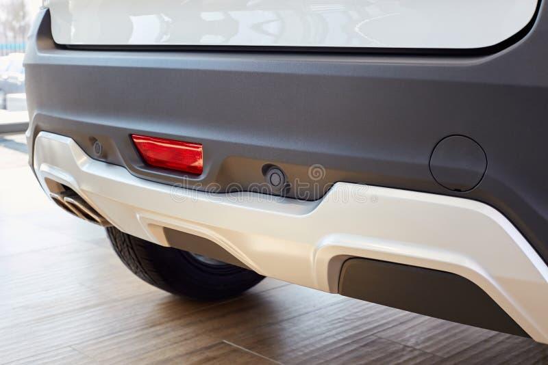 Parkende Sensoren auf einem weißen Auto, hinterer Stoßstange mit Reflektor- und Auspuffrohr und dem Platz, zum des Hakens für das stockbild
