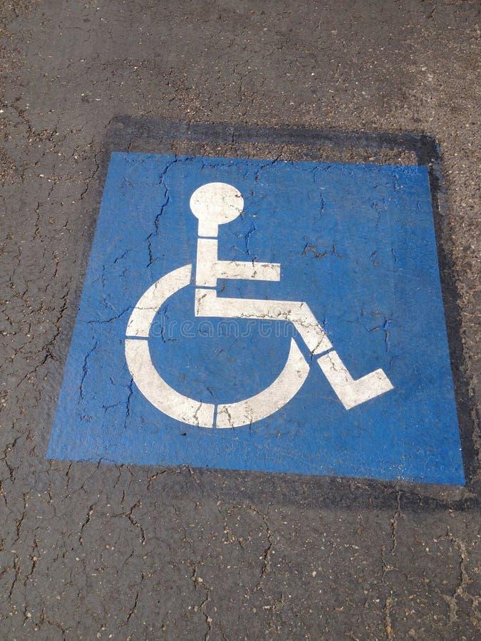 Parkendes Zeichen des blauen Handikaps mitten in einem schwarzen Asphalt stockbild