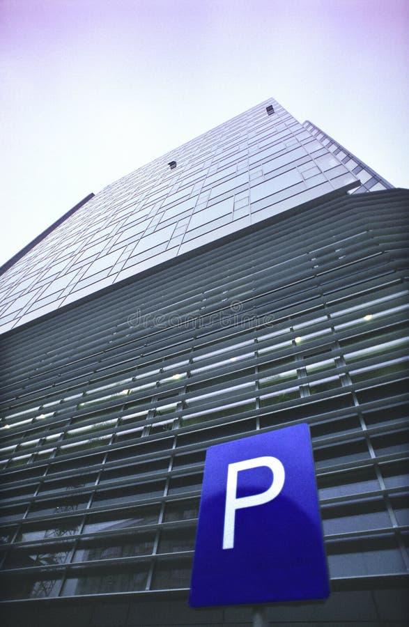 Parkenzeichen und Bürohaus stockbild
