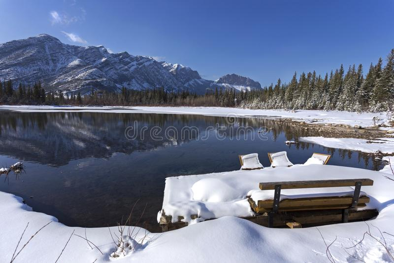 Parkera bänken och den snöig sjön i Alberta Foothills av kanadensiska steniga berg fotografering för bildbyråer