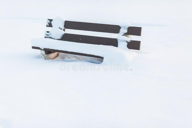 Parkera bänken under en kall vinter som täckas med högar av snö royaltyfri fotografi