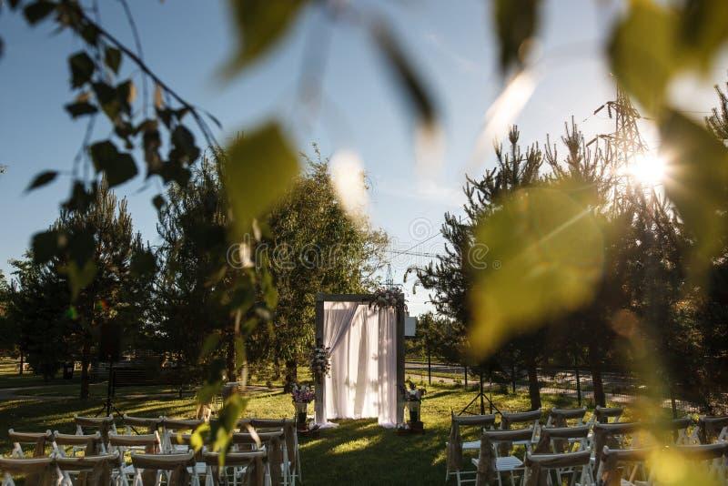 Parkera förberett för en gifta sig ceremoni Många rader av stolar på de båda sidorna av banan och träbågen i mitt royaltyfri foto
