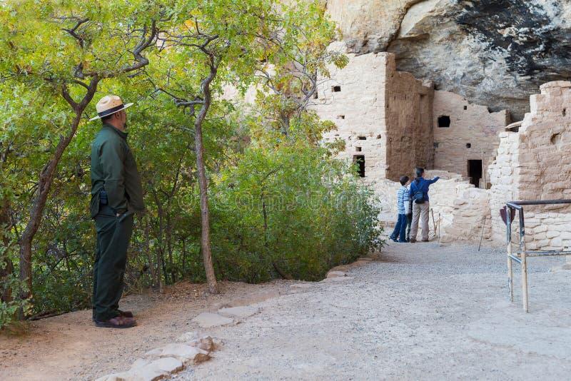 Parkera kommandosoldaten som ser modern och sonen som besöker Cliff Palace i Mesa Verde National Park royaltyfri bild