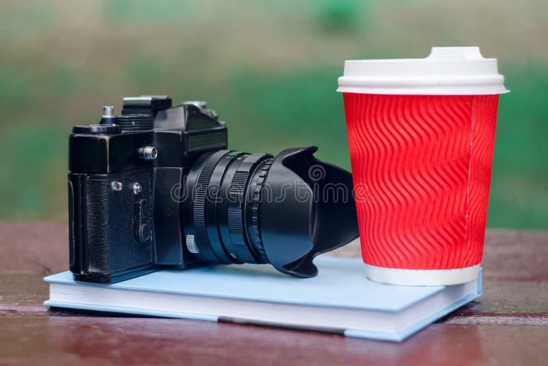 Parkera koppen för kaffe för boken för bänkbokkameran arkivbild