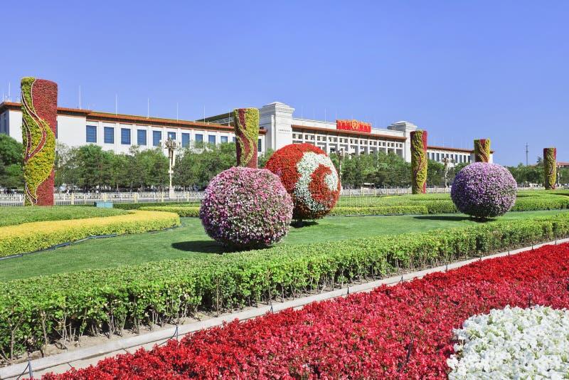 Parkera med färgrika blommor på den Tiananmen fyrkanten med det nationella museet, Peking, Kina arkivfoto