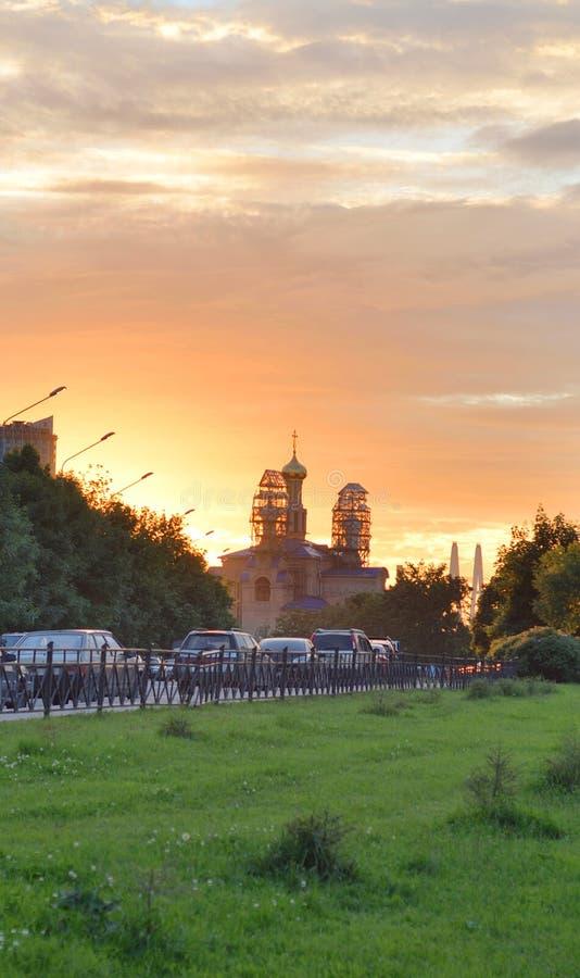 Parkera och den ortodoxa kyrkan på solnedgången royaltyfri fotografi