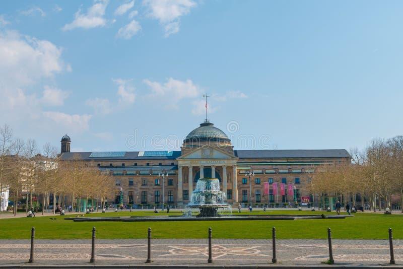 Parkera och springbrunnen framme av Kurhaus Wiesbaden royaltyfri fotografi