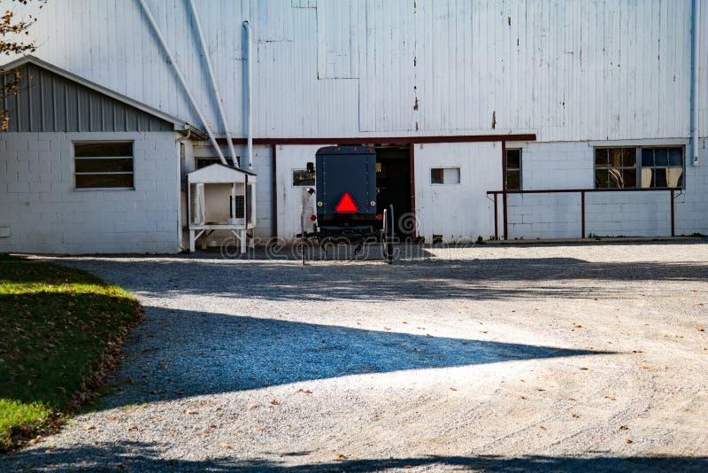 Parkerad Amish barnvagn nära den vita ladugården royaltyfri foto