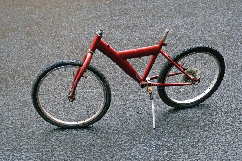 Parkerad röd cykel i regnet arkivbild