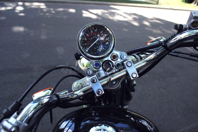 Parkerad retro kryssaremotorcykel i skuggan av en stadsgata fotografering för bildbyråer