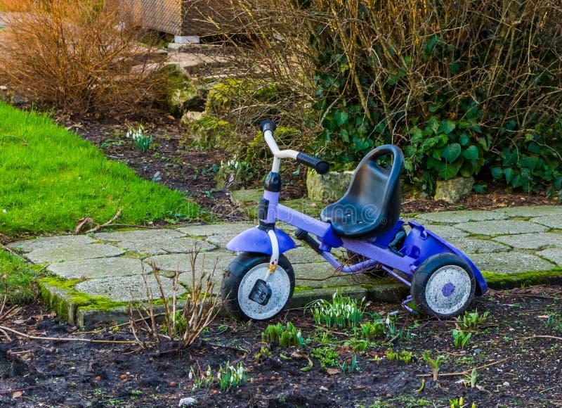 Parkerad trehjuling i trädgården, barnleksaker, populär ungeleksak arkivfoto