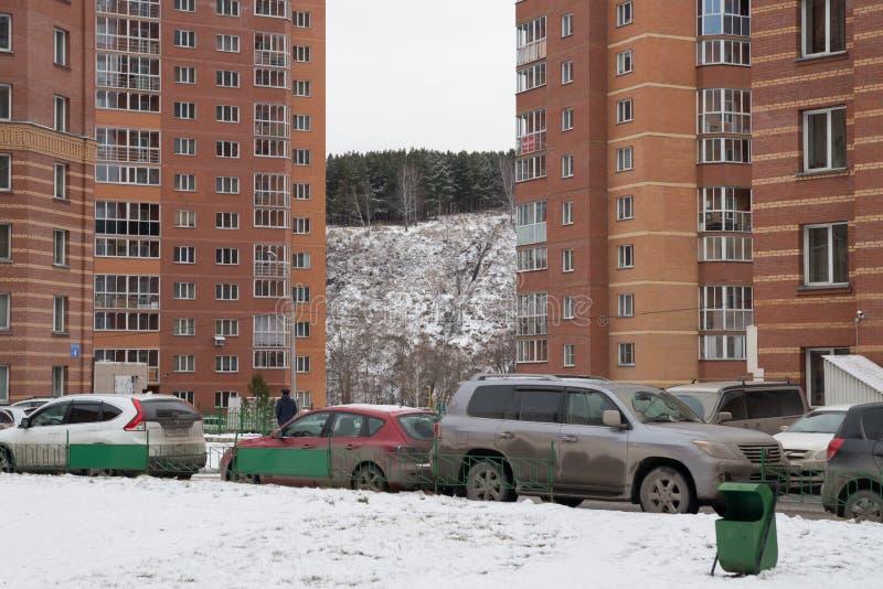 Parkerade bilar i gården mellan de bostads- byggnaderna av staden av Novosibirsk i vintern Novosibirsk region Ryssland arkivbild