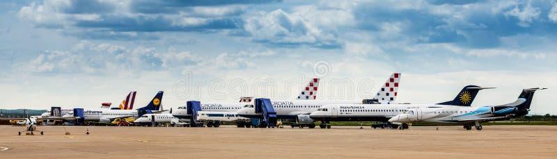 Parkerade flygplan på grov asfaltbeläggning av den Zagreb flygplatsen arkivfoto