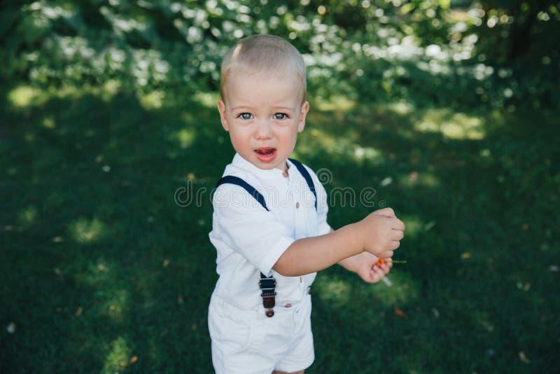 parkerar årigt barn 2 i, i vita kortslutningar och en vit T-tröja Den blonda pojken med bl?tt synar Gladlynt barn i arkivbild