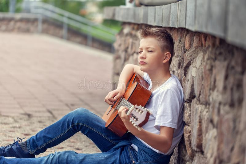 Parkerar den akustiska gitarren f?r ton?ringen som spelar sammantr?de p? momenten i royaltyfri fotografi