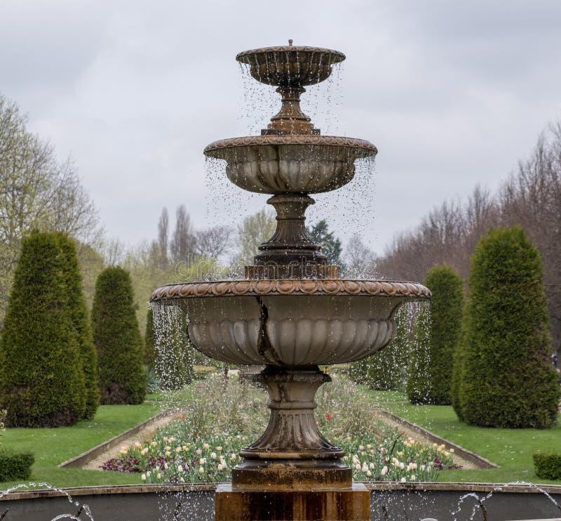 Parkerar den arrangementFormal blommaordningen för den formella blomman med vattenspringbrunnen i förgrund på härskande härskande royaltyfri fotografi