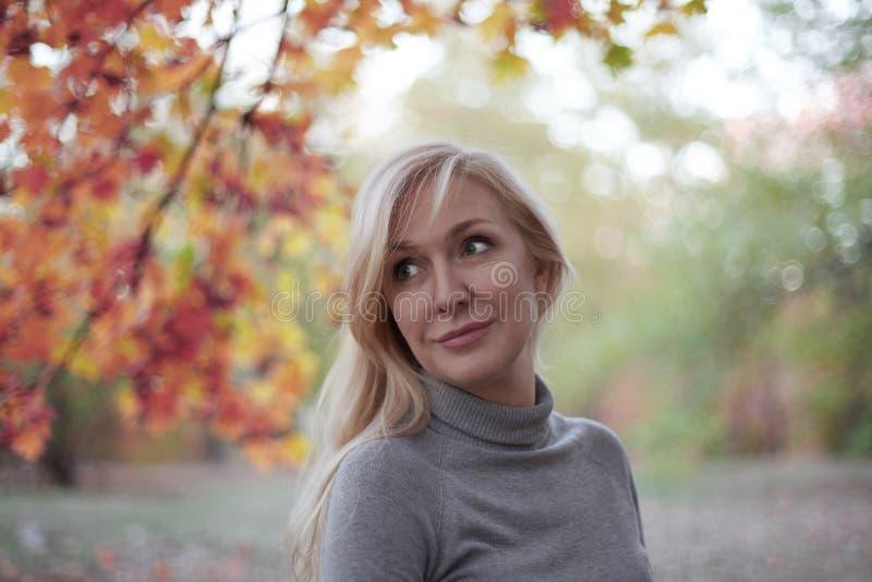 Parkerar den attraktiva mitt åldrades caucasian kvinnan med gröna ögon på hösten och att le, bara tillfällig wear Dyrbart ålderbe royaltyfri bild