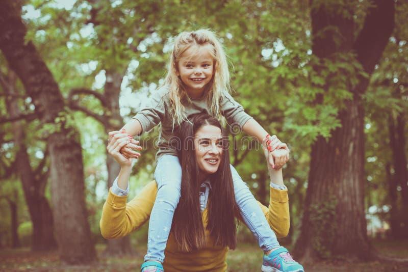 Parkerar den bärande dottern för modern på ridtur på axlarnaho royaltyfri bild