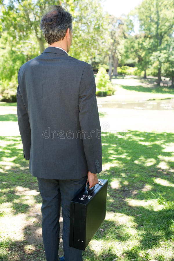 Parkerar den bärande portföljen för affärsmannen in royaltyfri foto