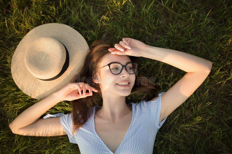 Parkerar den bästa sikten för närbilden av en flicka i att ligga på det gröna gräset Exponeringsglas och hatt Lycklig ungdomfriti arkivbild