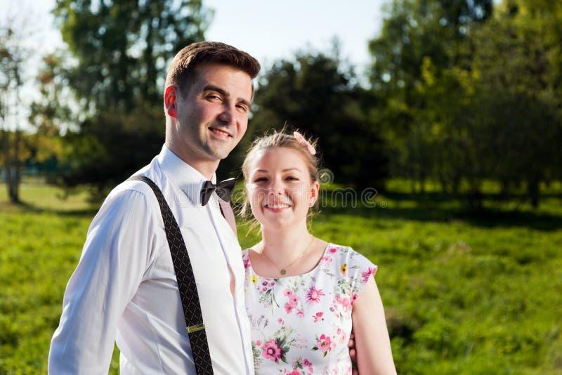 Parkerar den förälskade ståenden för unga lyckliga par i sommar arkivbilder