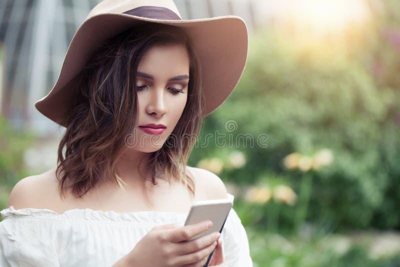 Parkerar den hållande ögonen på videoen för kvinnan i internet på celltelefonen in Flickastudent som pratar på den smarta telefon arkivfoton