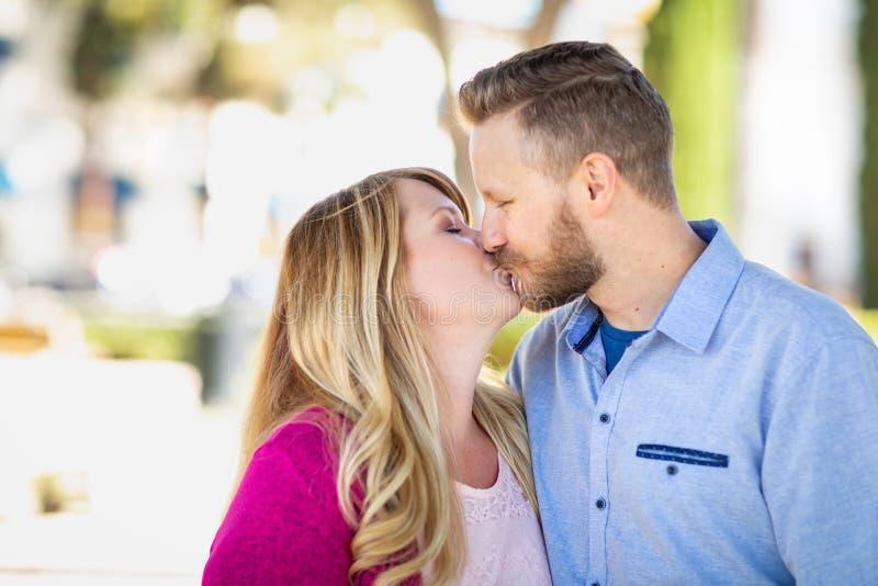 Parkerar den kyssande ståenden för unga vuxna Caucasian par på arkivfoton