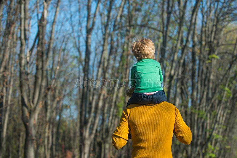 Parkerar den lilla sonen för faderhållen på skuldror som ger barnridtur på axlarna in På ryggen ritt Ta mig till överkanten royaltyfri fotografi